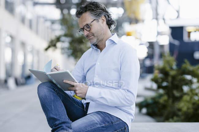 Portrait of smiling mature man with notebook — Fotografia de Stock