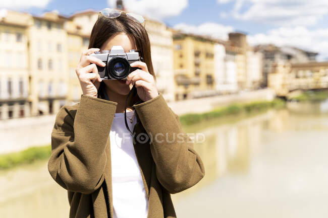 Italy, Florence, young tourist woman taking pictures at Ponte Vecchio — Foto stock