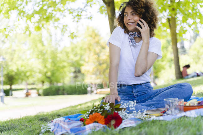 Relaxed woman on cell phone having a picnic in park — Stock Photo