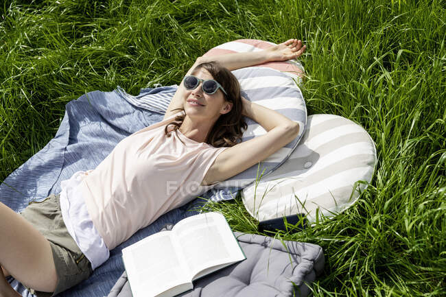 Relaxed woman with book lying on a meadow — Stock Photo
