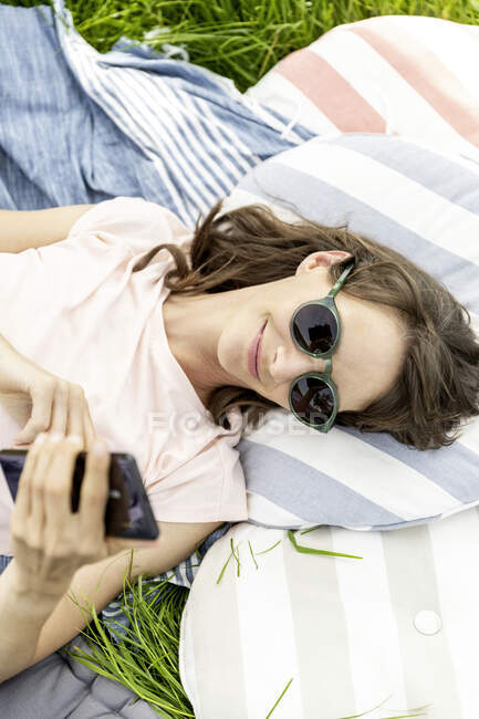 Relaxed woman lying on a meadow using cell phone — Stock Photo