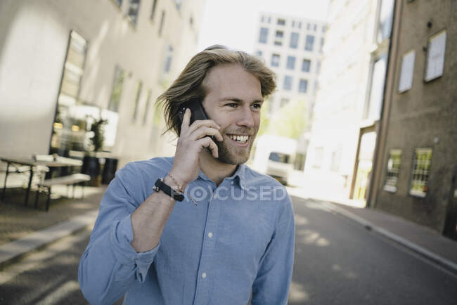 Smiling young man on cell phone in the city — Stock Photo