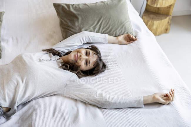 Mujer relajada acostada en la cama en casa - foto de stock