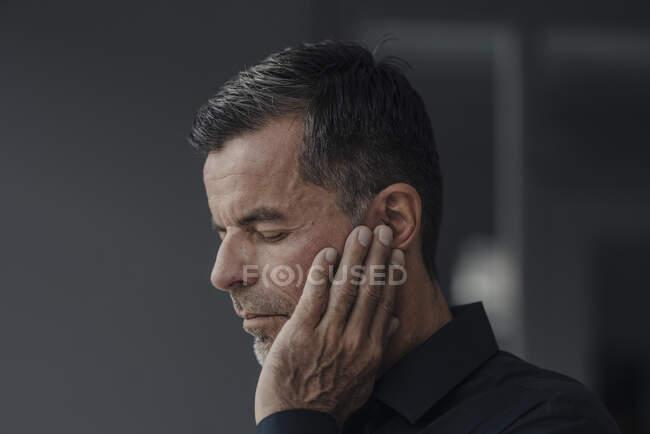 Portrait of mature businessman having earaches - foto de stock