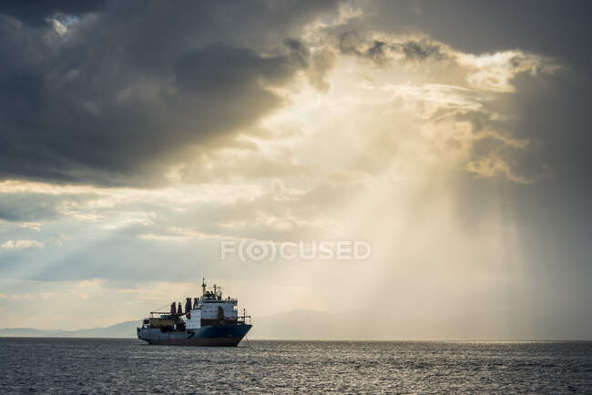 Ship before the sun breaking through the clouds above the Amur in Vladivostok, Russia — Stock Photo