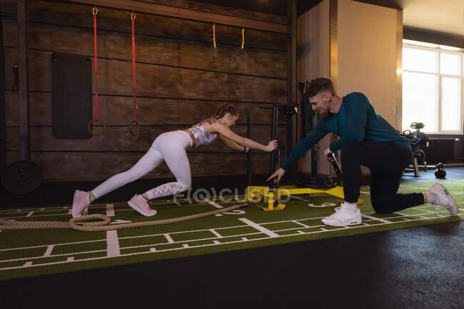 Молодая женщина, занимающаяся в тренажерном зале с личным тренером толкая сани — стоковое фото