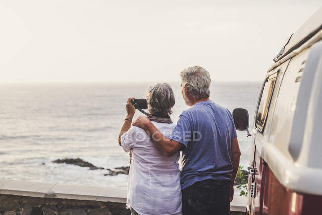 Senior couple traveling in a vintage van, taking pictures at the sea — Stock Photo