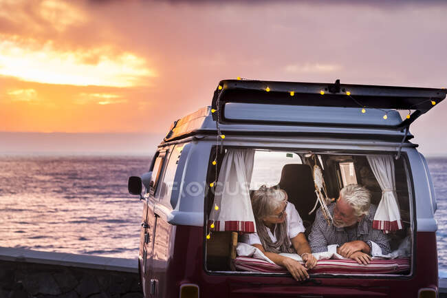 Senior couple traveling in a vintage van, lying in boot — Stock Photo
