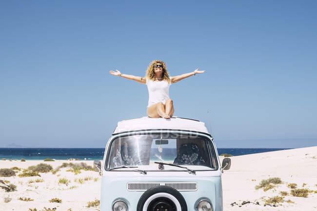 Жінка сидить на даху фургона