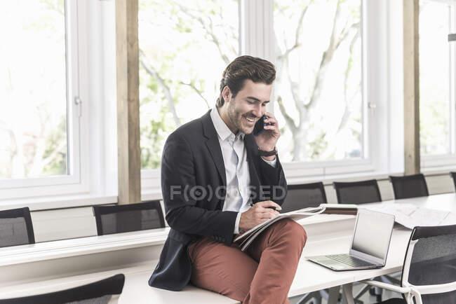 Jeune homme d'affaires assis dans la salle de réunion, parlant au téléphone — Photo de stock