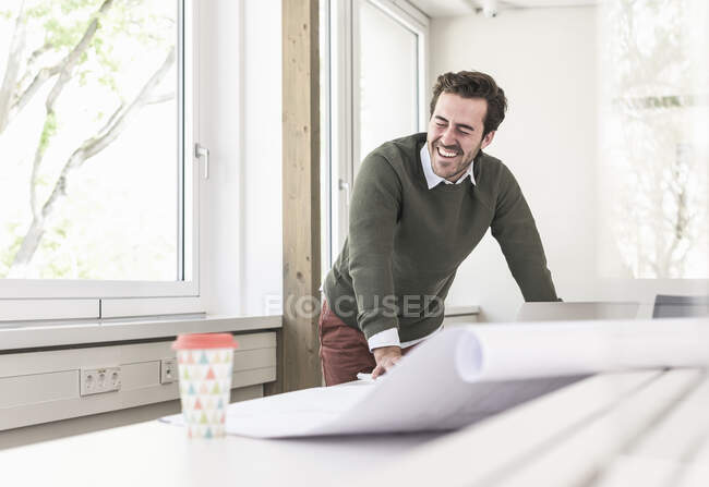 Laughing young architect working on blueprint in bright office — Stock Photo