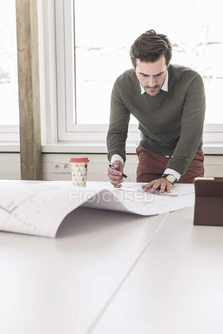 Young architect working on blueprint in bright office — Stock Photo