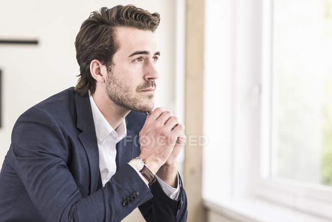 Застенчивый бизнесмен, сидящий у окна — стоковое фото