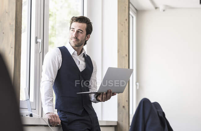 Businessman standing at the window, using laptop — Stock Photo