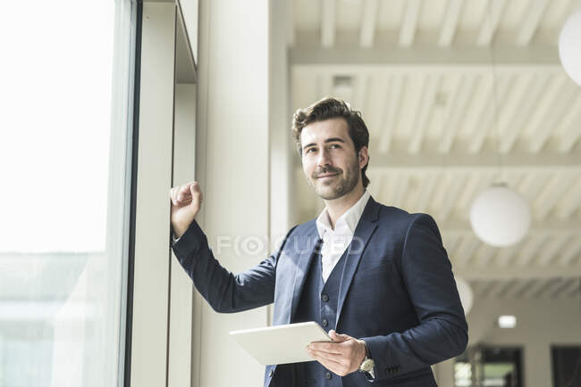 Successful manager standing in modern office building, using laptop — Stock Photo