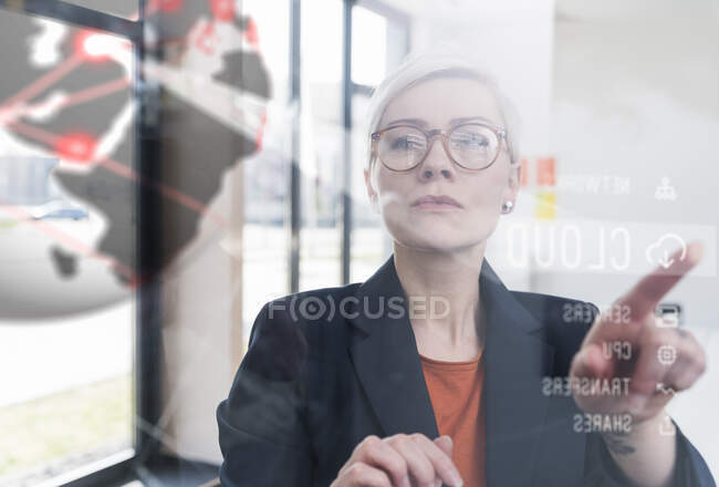 Businesswoman touching glass wall with data in office — Stock Photo