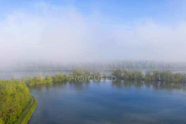 Niebla matutina en el embalse de Altheim, Isar, cerca de Landshut, Baviera, Alemania, disparo de drones - foto de stock