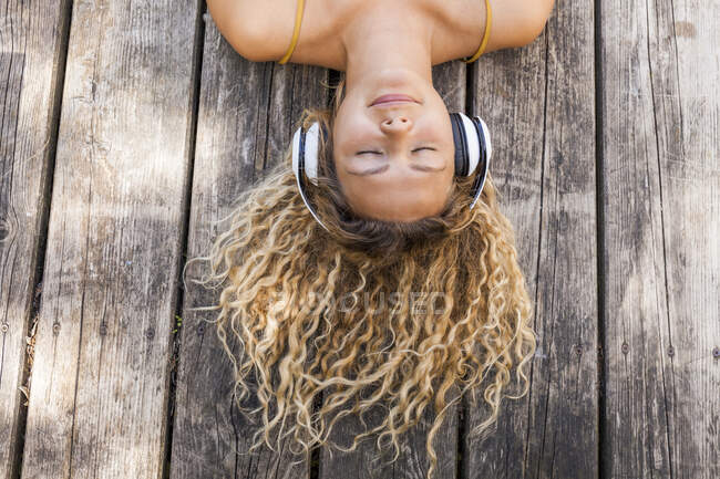 Smiling woman listening to music, lying on wood — Stock Photo
