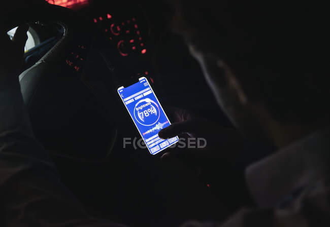 Close-up of young man adjusting brightness of cell phone in car at night — Stock Photo