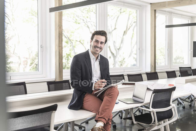 Young businessman sitting in boardroom, preparing for presentation — Stock Photo