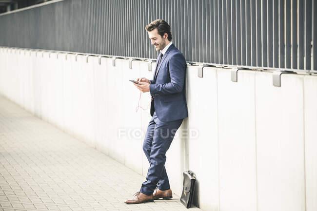 Бізнесмен сперся на стіну в міському телефоні. — стокове фото
