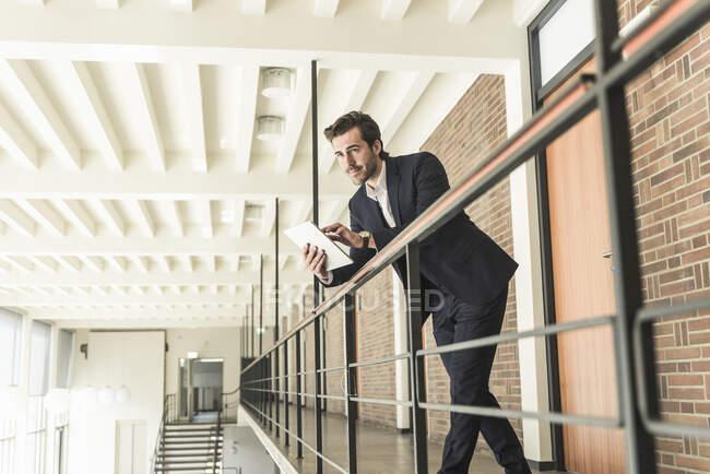 Молодий бізнесмен стоїть у галереї в сучасному офісному будинку, користуючись цифровою табличкою. — стокове фото