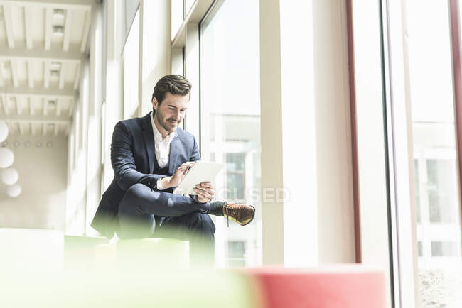 Young businessman sitting in lounge, using digital tablet — Stock Photo
