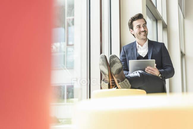 Jeune homme d'affaires assis dans le salon, en utilisant une tablette numérique — Photo de stock