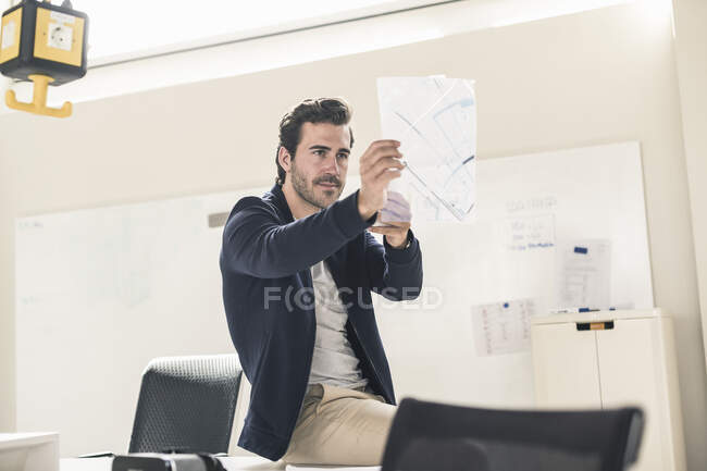 Young businessman in office holding foil of a blueprint — Stock Photo