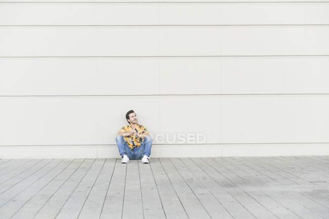 Young man wearing aloha shirt, sitting on ground, thinking — Stock Photo