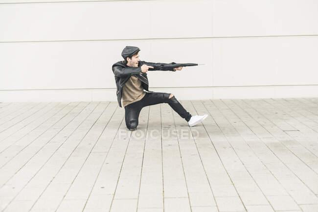 Joven fingiendo disparar con un paraguas cerrado - foto de stock