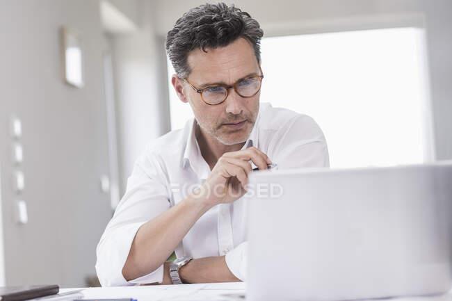 Empresário trabalhando em escritório brilhante, usando laptop — Fotografia de Stock