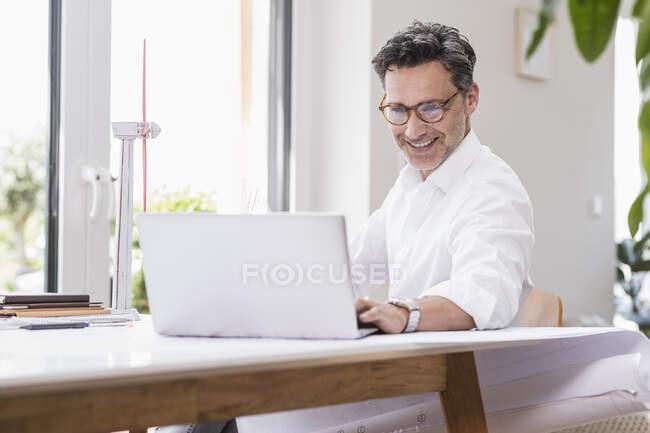 Бізнес n сидячи в офісі, використовуючи ноутбук, дивлячись на модель вітрового колеса — стокове фото