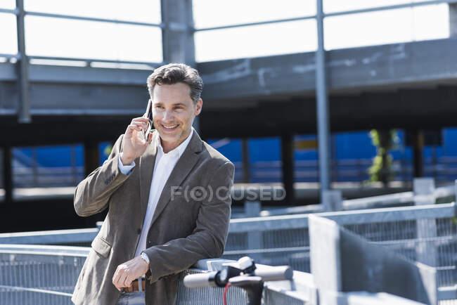 Бізнесмен за допомогою смартфона, E-Scooter спирається на поручні — стокове фото