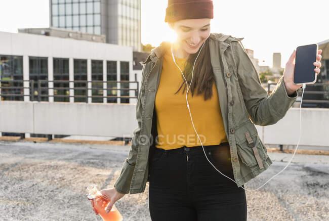 Jovem feliz com fones de ouvido dançando no deck de estacionamento ao pôr do sol — Fotografia de Stock