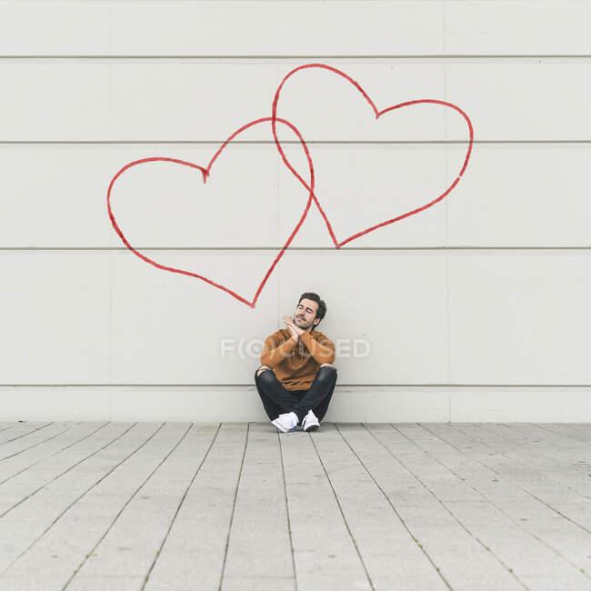 Цифровая композиция молодого человека, сидящего у стены с сердцем — стоковое фото