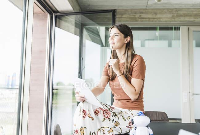 Молода бізнесменка, яка сидить за столом у офісі, думає — стокове фото