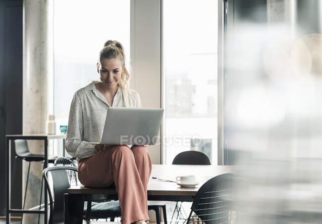 Безробітна жінка сидить за столом у офісі за допомогою ноутбука. — стокове фото