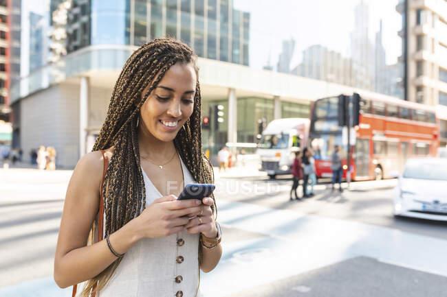 Retrato de uma jovem sorridente na cidade olhando para o telefone celular, Londres, Reino Unido — Fotografia de Stock