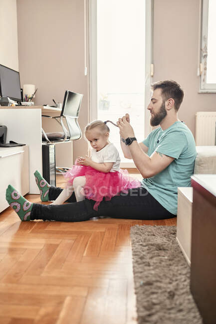Padre trenzando el pelo de su hija - foto de stock