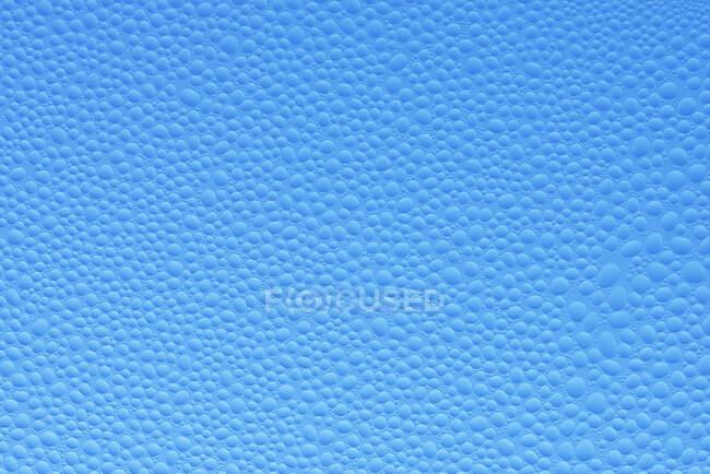 Gotas de agua en una ventana de cristal de un coche contra el cielo azul claro, primer plano - foto de stock