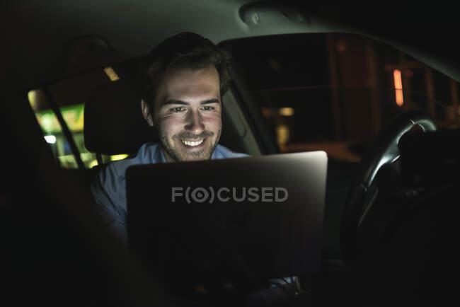 Lächelnder junger Mann nutzt Laptop in der Nacht im Auto — Stockfoto