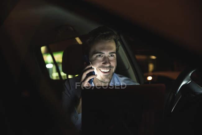 Щасливий молодий чоловік на мобільному телефоні вночі. — стокове фото