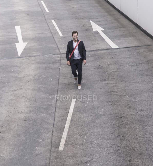 Hombre de negocios seguro caminando por la carretera con señales de flecha - foto de stock