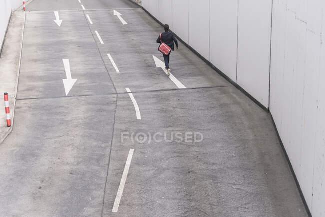 Rückansicht Geschäftsmann läuft mit Pfeil auf Straße — Stockfoto