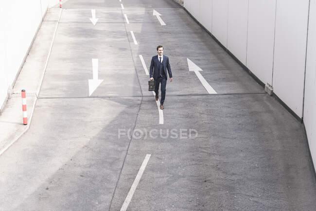 Geschäftsmann läuft mit Pfeil auf Straße — Stockfoto