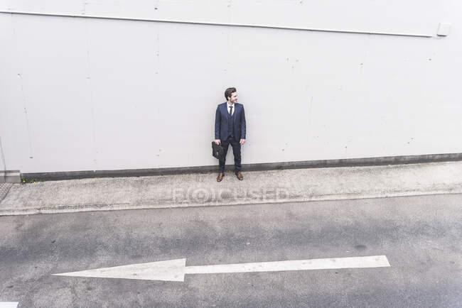 Бизнесмен, стоящий на дороге со стрелкой — стоковое фото