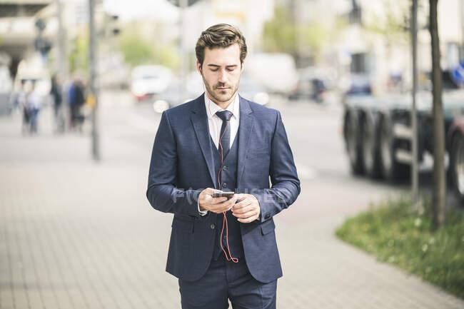 Бизнесмен, гуляющий по городу с помощью мобильного телефона — стоковое фото