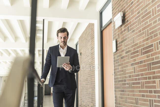 Jungunternehmer steht mit digitalem Tablet auf Empore in modernem Bürogebäude — Stockfoto