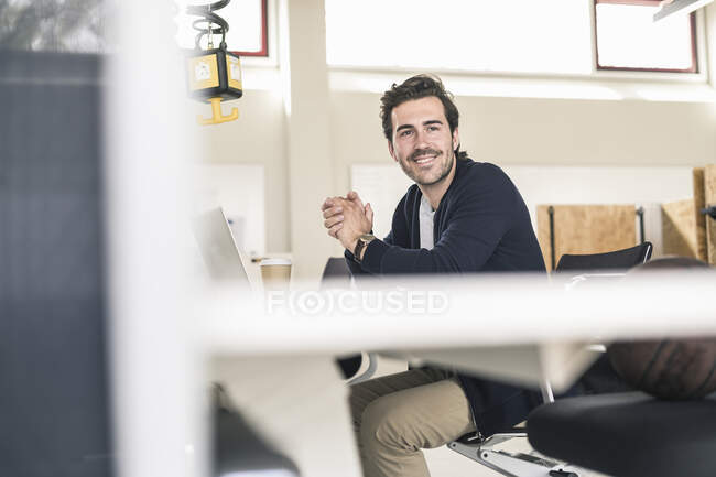 Young businessman sitting in office, using laptop — Stock Photo